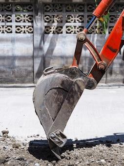 Cuchara de excavadora cavando en el suelo para la construcción de carreteras en la aldea