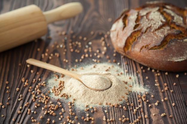 Cuchara con harina de trigo sarraceno y un pan sobre un fondo de madera. harina alternativa. alimentación sana y sin gluten.