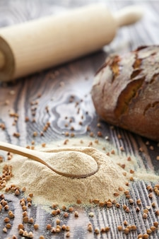 Cuchara con harina de trigo sarraceno sobre un fondo de madera. concepto de harina alternativa. alimentación sana y sin gluten.