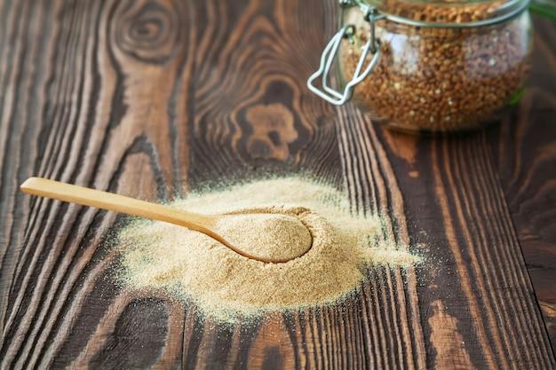 Cuchara con harina de trigo sarraceno sobre una madera.