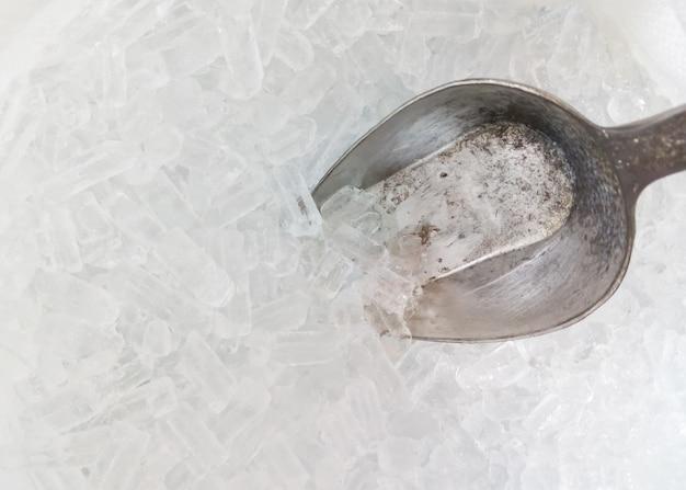 Cuchara de hielo de metal en el pequeño cubo de hielo.