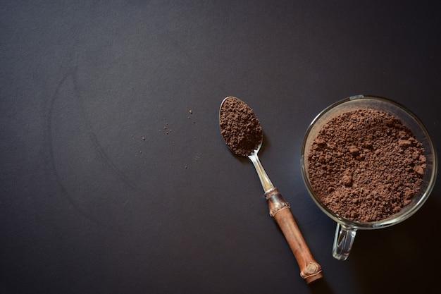 Cuchara llena de café en polvo sobre fondo negro.