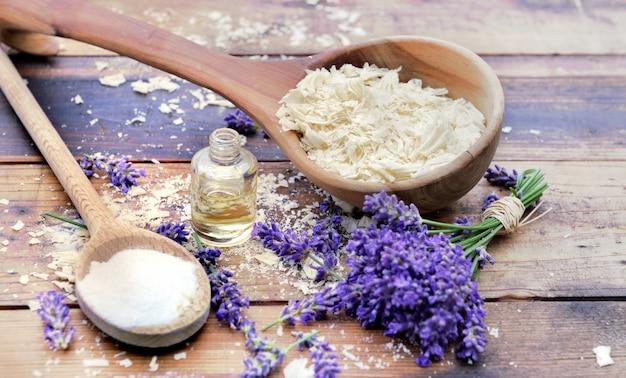 Cuchara llena de escamas de jabón con aceite esencial y racimo de flores de lavanda y bicarbonato de sodio sobre una superficie de madera.