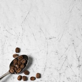 Cuchara llena de granos de café y espacio de copia