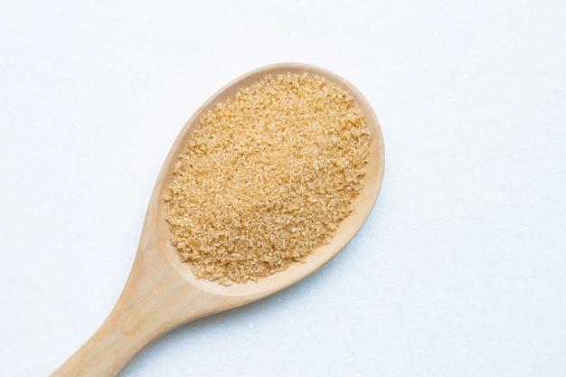 Cuchara de madera con azúcar moreno sobre azúcar granulada blanca.