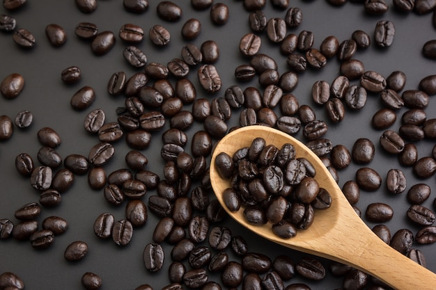 Cuchara de madera con café tostado en grano.