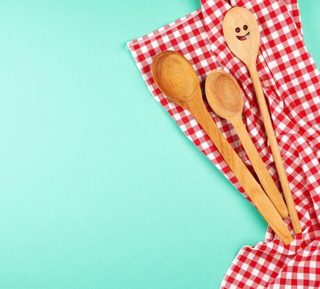 Cuchara de madera con una cara tallada sobre una toalla de cocina roja