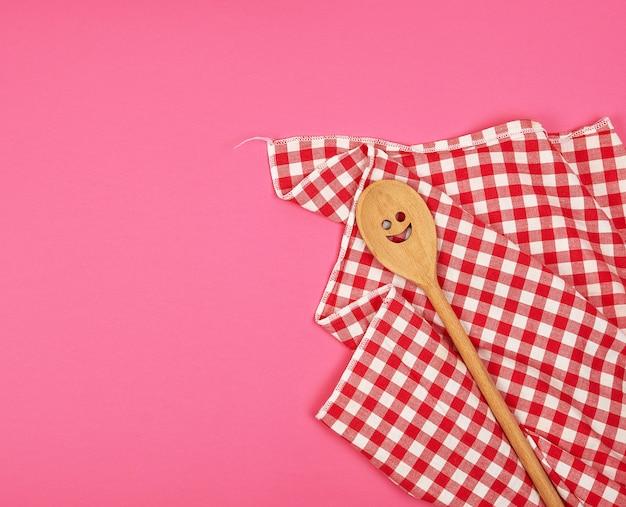 Cuchara de madera con una cara tallada en una toalla de cocina roja