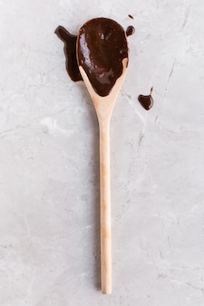 Cuchara de madera en chocolate líquido sobre un fondo blanco.