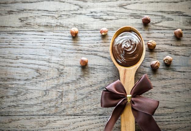 Cuchara de madera con crema de chocolate y avellanas.