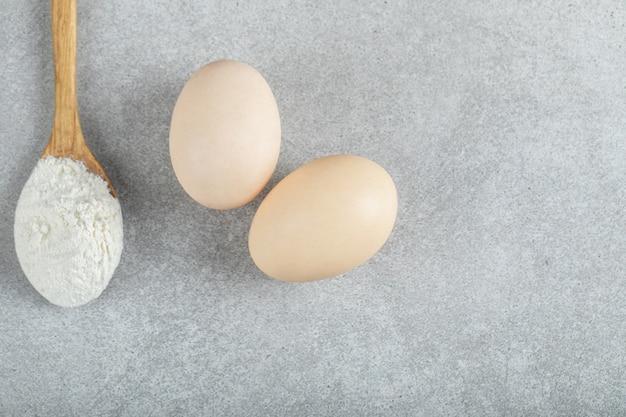 Una cuchara de madera con harina y huevos de gallina.
