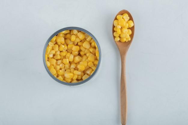 Una cuchara de madera llena de semillas de palomitas de maíz en blanco.