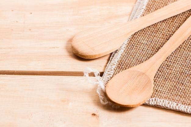 Cuchara de madera puesta en saco y fondo de mesa de madera en la cocina casera