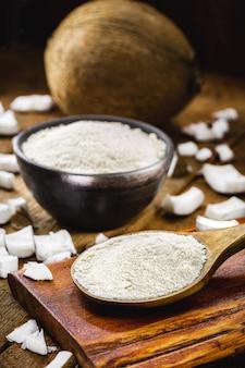 Cuchara de madera rústica completa y harina de coco, sobre mesa de madera con coco en el fondo, ingrediente culinario.