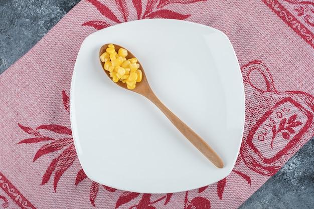 Una cuchara de madera de semillas de palomitas de maíz en un plato vacío.