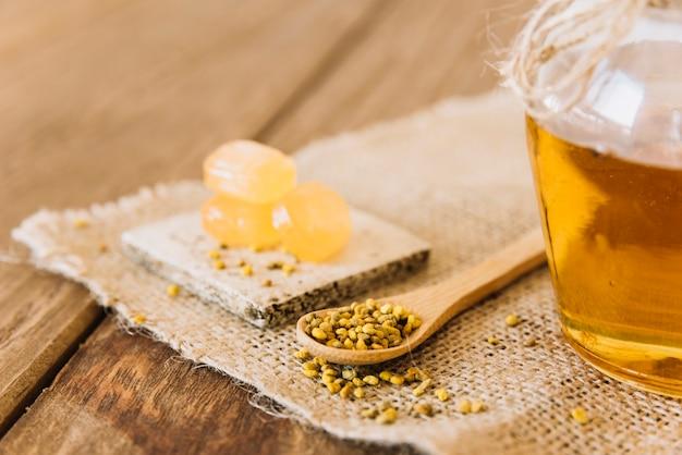 Cuchara de madera; semillas de polen de abeja; caramelos y tarro de miel sobre tela de saco.