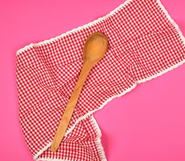 Cuchara de madera sobre una toalla de cocina roja, fondo rosa