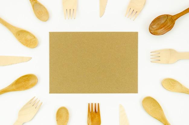 Cuchara de madera y tenedor sobre fondo blanco.