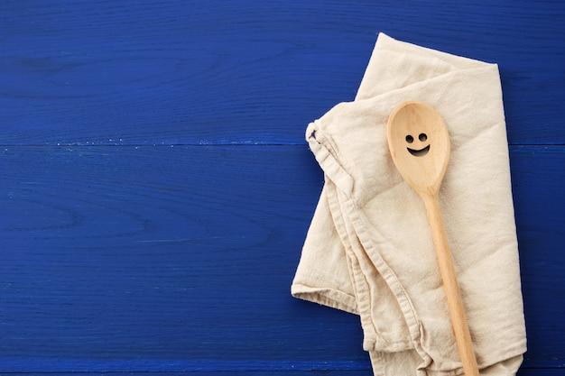 Cuchara de madera vintage y toalla de cocina textil blanco sobre fondo de madera azul