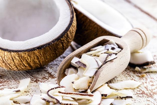 Cuchara medidora de madera con trozos y virutas de coco, ingrediente de cocina.