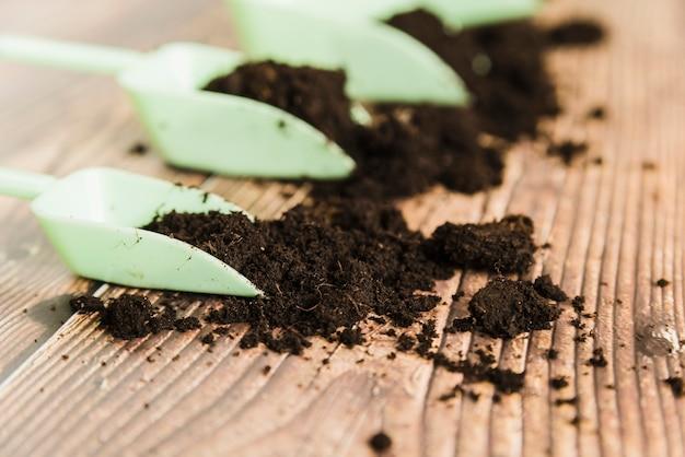 Cuchara medidora con suelo fértil sobre superficie de madera.