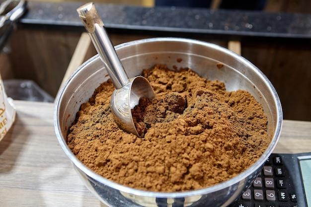 Cuchara medidora en un tazón de café molido tostado en el mostrador de la cafetería.