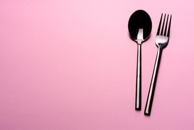 Cuchara de metal y tenedor en mesa rosa. conjunto de vajilla listo para la comida con espacio de copia rosa