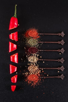 Cuchara de metal con varias especias de pimienta en rodajas vista superior de ají rojo