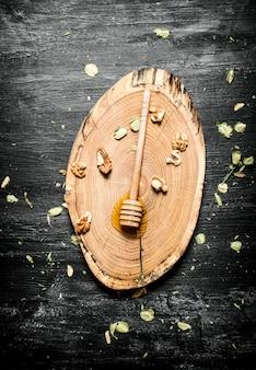 Cuchara de miel fresca sobre una tabla de madera sobre fondo rústico negro