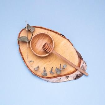 Cuchara de miel con tazón de madera sobre fondo azul.