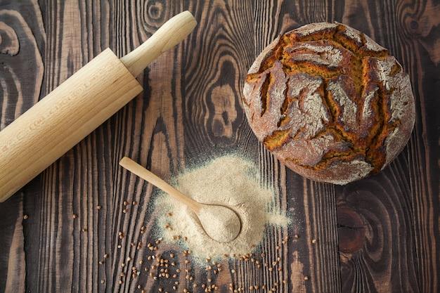 Cuchara plana con harina de trigo sarraceno, rodillo y pan sobre una mesa de madera
