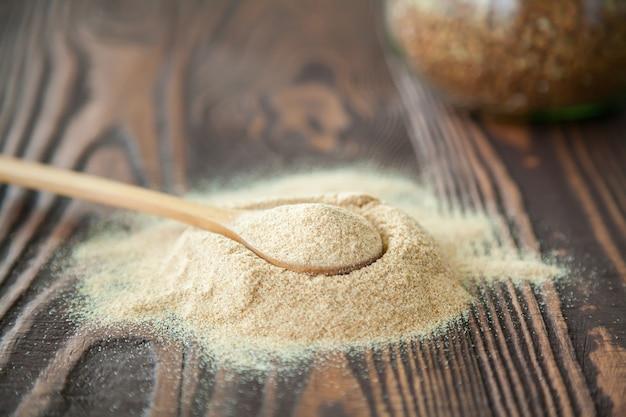 Cuchara de primer plano con harina de trigo sarraceno en una madera