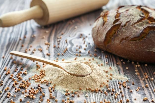 Cuchara de primer plano con harina de trigo sarraceno, un pan y un rodillo sobre un fondo de madera. harina alternativa. alimentación sana y sin gluten.