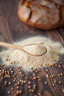 Cuchara de primer plano con harina de trigo sarraceno sobre un fondo de madera. harina alternativa.