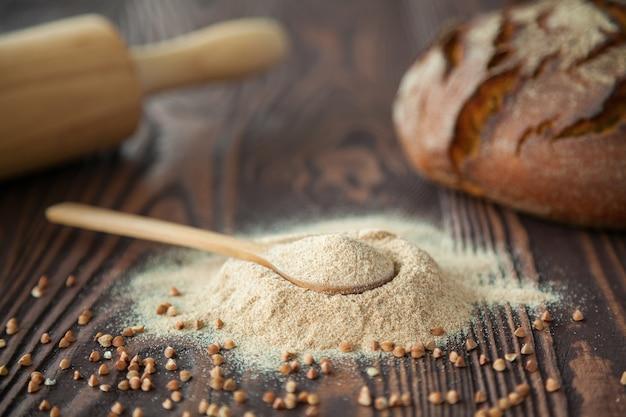 Cuchara de primer plano con harina de trigo sarraceno sobre una superficie de madera. harina alternativa. alimentación sana y sin gluten.