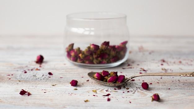 Cuchara de primer plano con mini rosas aromáticas