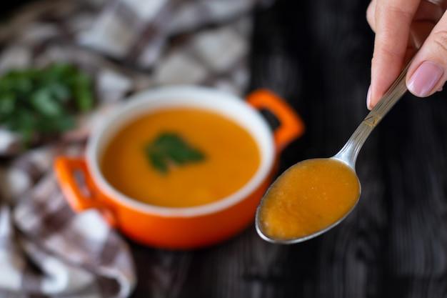 Cuchara de sopa de crema de zanahoria y calabaza en un plato de naranja con queso pita sobre un mantel a cuadros
