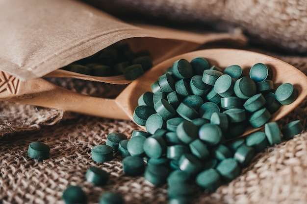 Cuchara en tabletas de alga espirulina en tabletas sobre un fondo oscuro de arpillera. súper comida vegana
