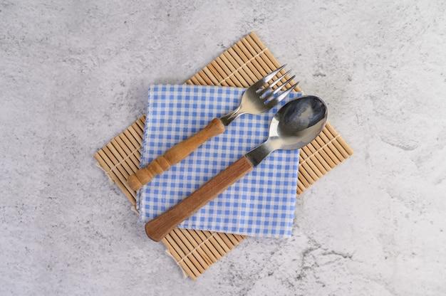 Cuchara y tenedor colocados en pañuelos azules y blancos.