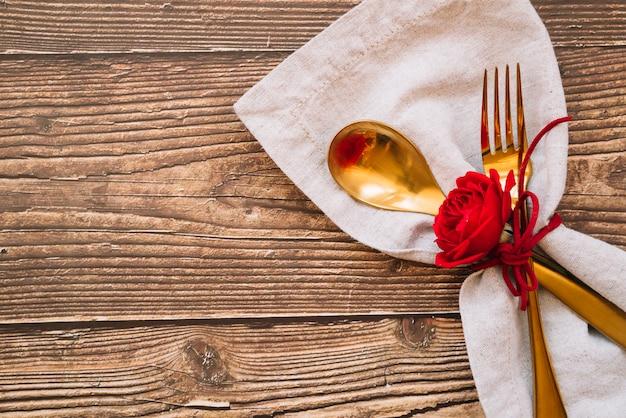Cuchara y tenedor con flor roja en servilleta.