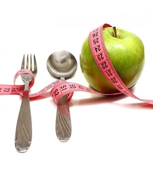 Cuchara tenedor y manzana se ensarta con una cinta para medir la dieta.