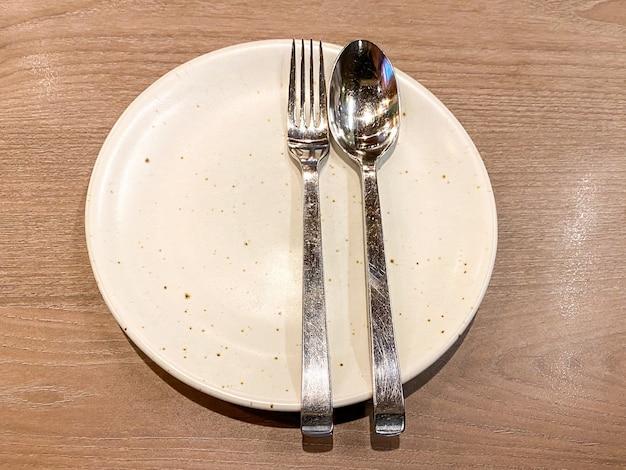 Cuchara y tenedor de metal en placa de cerámica sobre la mesa