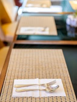 Cuchara y tenedor organizados en la mesa durante el desayuno ubicado en bandung, indonesia