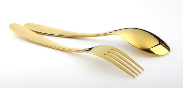 La cuchara y el tenedor de oro elegantes y costosos se colocan en un fondo blanco.