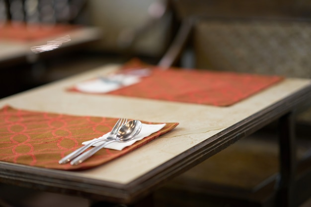 Cuchara y tenedor en la preparación de la mesa para la comida comida en el restaurante