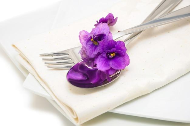 Una cuchara con un tenedor sobre una servilleta y un plato decorado con violetas.