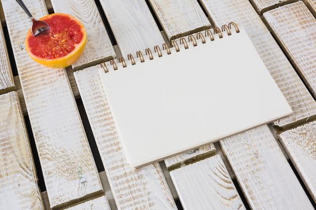 Cuchara en la toronja a la mitad con cuaderno espiral sobre fondo de patrón