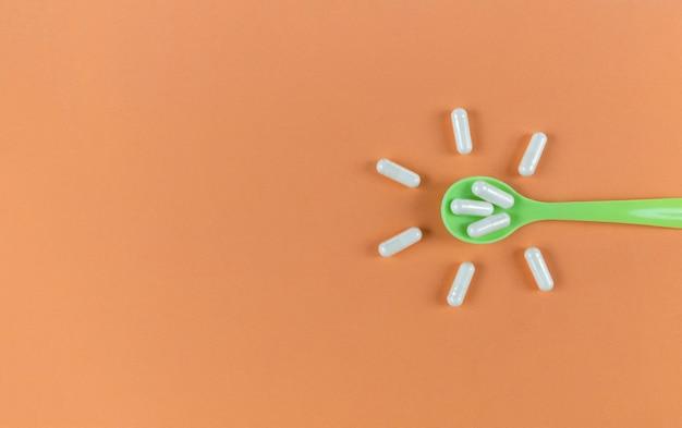 Cuchara verde y cápsulas blancas sobre un fondo naranja con espacio de copia.