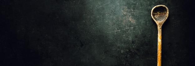 Cuchara vieja en la mesa oscura