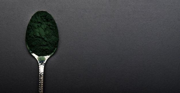 Cuchara de vista superior con especias verdes orgánicas y espacio de copia